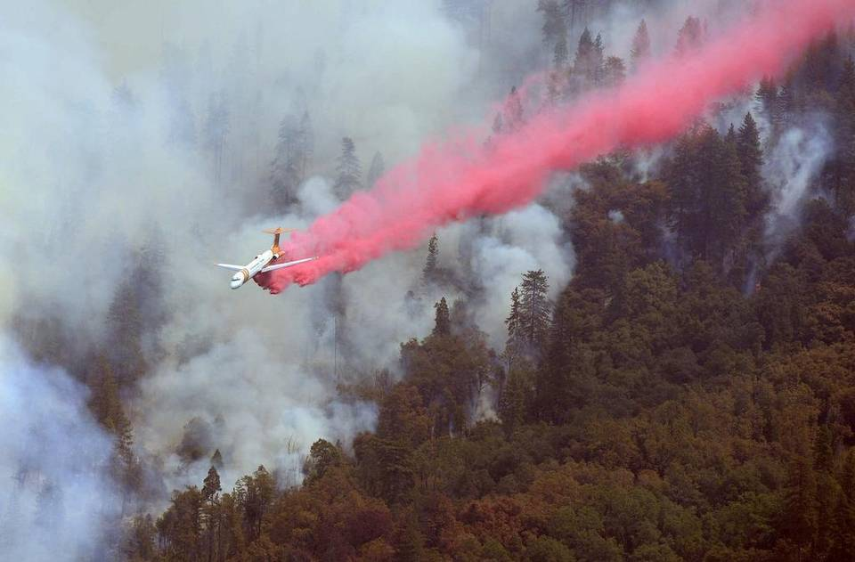 Plane spreading red fire retardant over a forest with smoke